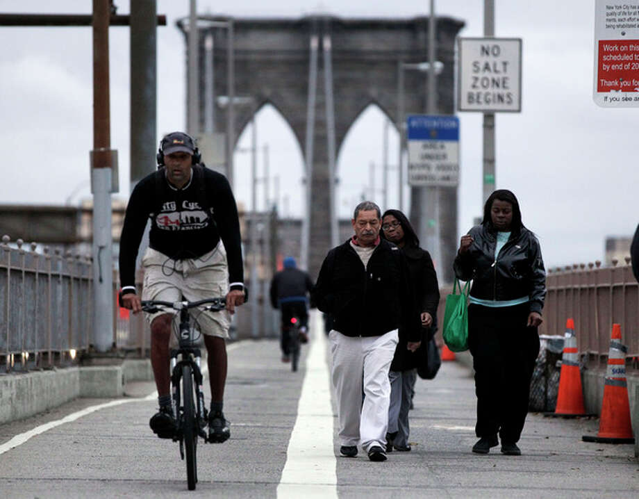 FILE - In this Oct. 31, 2012 file photo, morning commuters walk and bicycle across New York's Brooklyn Bridge. On the Brooklyn Bridge, closed earlier because of high winds, joggers and bikers made their way across the span before sunrise. Car traffic on the bridge was busy, and slowed as it neared Manhattan. Nearly every office dweller fantasizes about the joys of working from home, but Superstorm Sandy has created legions of people who can't wait to get back to the office. (AP Photo/Richard Drew, File) / AP