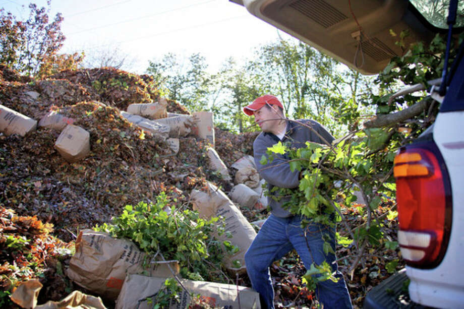 John Herrington dumps debri from Sandy at the Yard Waste Station in Norwalk Saturday morning.Hour Photo / Danielle Robinson