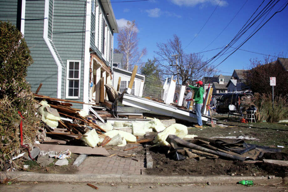 Hour photo / Danielle RobinsonA crew works on making repairs to a home Saturday morning in Norwalk. The home was damaged by Hurricane Sandy.