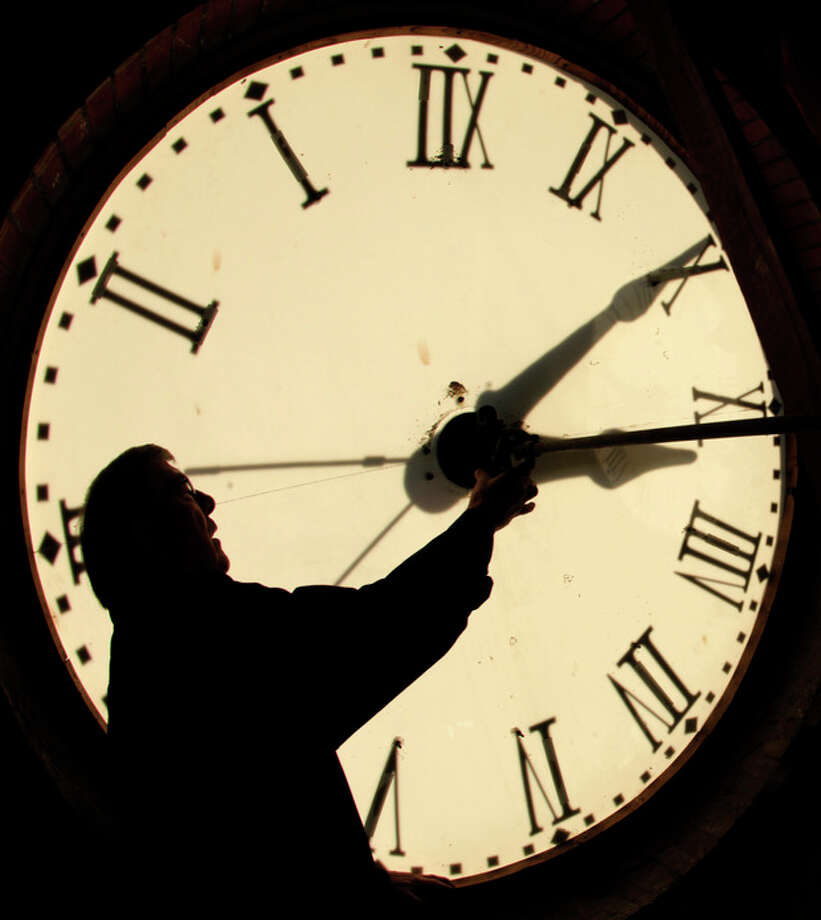FILE - Custodian Ray Keen checks the time on a clock face after changing the time on the 97-year-old clock atop the Clay County Courthouse, in this Nov. 6, 2010 file photo taken in Clay Center, Kan. Most Americans will be able to get an extra hour of sleep Sunday Nov. 4, 2012 thanks to the annual shift back to standard time. Officially, the change occurs at 2 a.m. Sunday, but most people will set their clocks back before hitting the sack Saturday night. (AP Photo/Charlie Riedel, File) / AP
