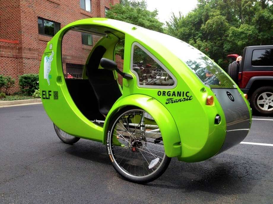 """This photo taken July 24, 2013 shows the Organic Transit's ELF bike in a parking lot in Reston, Va. It's the closest thing yet to Fred Flintstone's footmobile _ only with solar panels and a futuristic shape. It's an """"Organic Transit Vehicle,"""" a car-bicycle blend also known as an ELF bike, and 65-year-old family therapist Mark Stewart is taking it on a 1,200-mile journey along the East Coast Greenway, a bike and pedestrian trail that runs from Florida to Canada. (AP Photo/Valerie Bonk) / AP"""