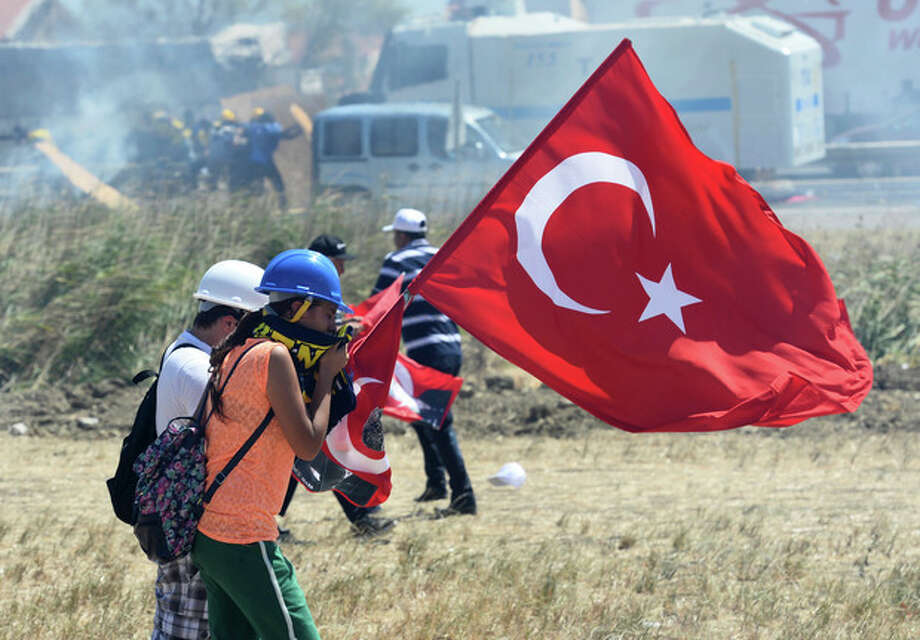 """People try to protect themselves as riot and paramilitary police officers fire tear gas and use water cannons to disperse protesters outside the Silivri jail complex in Silivri, Turkey, Monday, Aug. 5, 2013. Some 275 people - including military officers, politicians and journalists - are facing verdicts in a landmark and divisive trial in Turkey over an alleged conspiracy to overthrow the government. The court has acquitted 21 people accused of plotting to overthrow the Islamist-rooted government in the five-year """"Ergenekon"""" trial and sentenced of up to 47 years or life terms in jails some of the other 254 defendants.(AP Photo) / AP"""