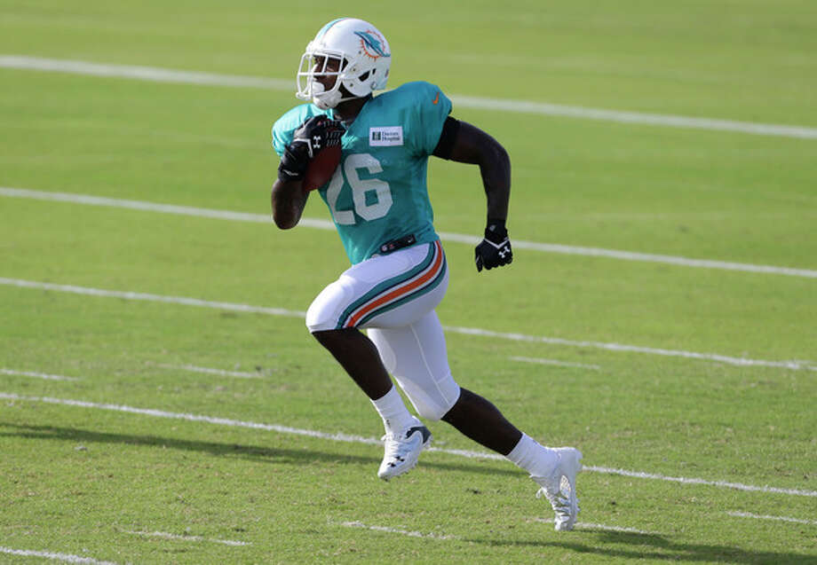 FILE - In this July 24, 2013 file photo, Miami Dolphins running back Lamar Miller (26) runs with the ball during an NFL football practice in Davie, Fla. Miller thinks he's ready to make a significant leap with the Miami Dolphins. He carried the ball just 51 times as a rookie last season, yet is widely expected to be the Dolphins' starting running back this season. (AP Photo/Lynne Sladky, File) / AP