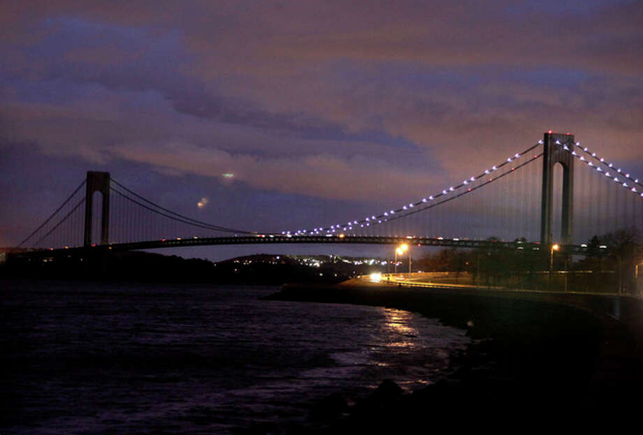 The half of the Verrazano Narrows Bridge attached to Brooklyn is lit while the half attached to Staten Island is dark in New York, Friday, Nov. 2, 2012. The massive storm that started out as Hurricane Sandy slammed into the East Coast and morphed into a huge and problematic system, killing at least 96 people in the United States. Power outages now stand at more than 3.6 million homes and businesses, down from a peak of 8.5 million. The cost of the storm could exceed $18 billion in New York alone. (AP Photo/Seth Wenig) / AP
