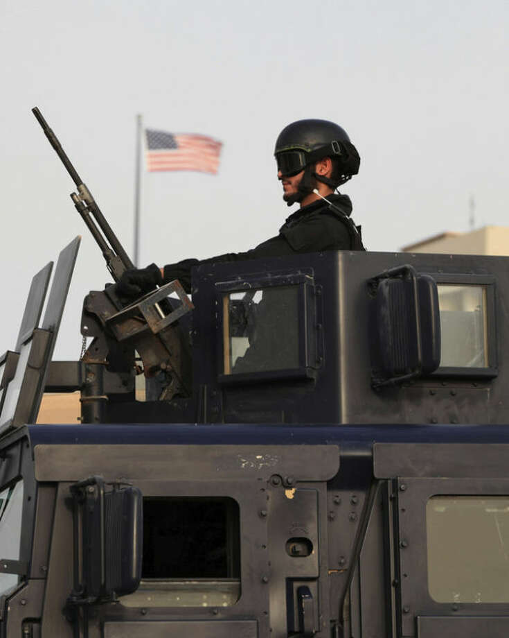 A Bahraini armored personnel vehicle and personnel reinforce U.S. Embassy security just outside of a gate to the building in Manama, Bahrain, on Sunday, Aug. 4, 2013. Security forces close access roads, put up extra blast walls and beef up patrols near some of the 21 U.S. diplomatic missions in the Muslim world that Washington ordered closed for the weekend over a ``significant threat'' of an al-Qaida attack. (AP Photo/Hasan Jamali)