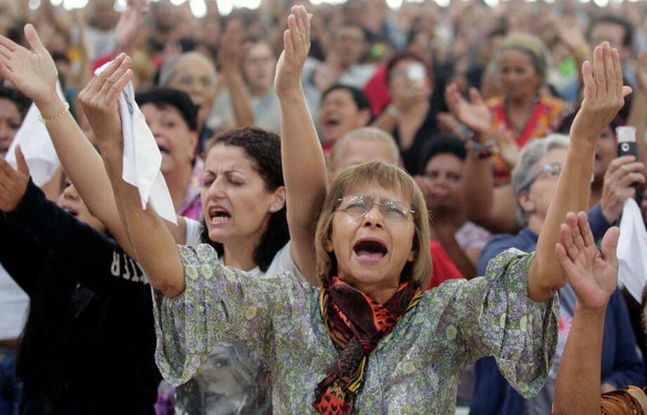 People attend a Mass led by Catholic priest Marcelo Rossi at the Mother of God sanctuary in Sao Paulo, Brazil, Saturday, Nov. 3, 2012. Rossi, a Latin Grammy-nominated Christian music singer and author of best-selling books in Brazil, inaugurated on Friday the massive new Roman Catholic church that will hold about 20,000 worshippers when complete. (AP Photo/Andre Penner) / AP
