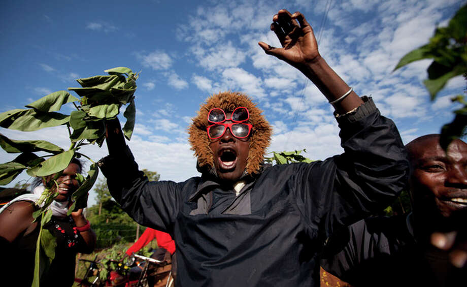 Villagers cheer and wave branches to celebrate Obama's re-election in the village of Kogelo, home to Sarah Obama, the step-grandmother of President Barack Obama, in western Kenya Wednesday, Nov. 7, 2012. (AP Photo/Ben Curtis) / AP