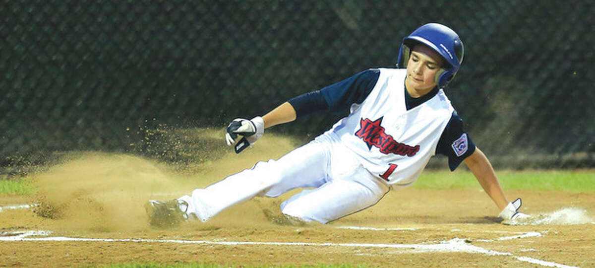 Hour Photo/Chris Palermo Westport's Christopher Drbal is safe at home during their 12-2 victory over Rye, N.H., in the Little League Baseball New England Regional Tournament on Monday night at the Giamatti Little League Center in Bristol.