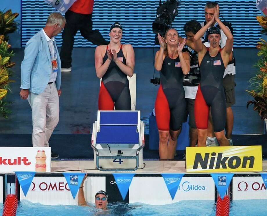 The United States Women's 4x100m medley relay team, from left: Missy Franklin, Jessica Hardy and Dana Vollmer celebrate after Megan Romano, in the water. anchored them to the gold medal at the FINA Swimming World Championships in Barcelona, Spain, Sunday, Aug. 4, 2013. (AP Photo/Daniel Ochoa de Olza) / AP