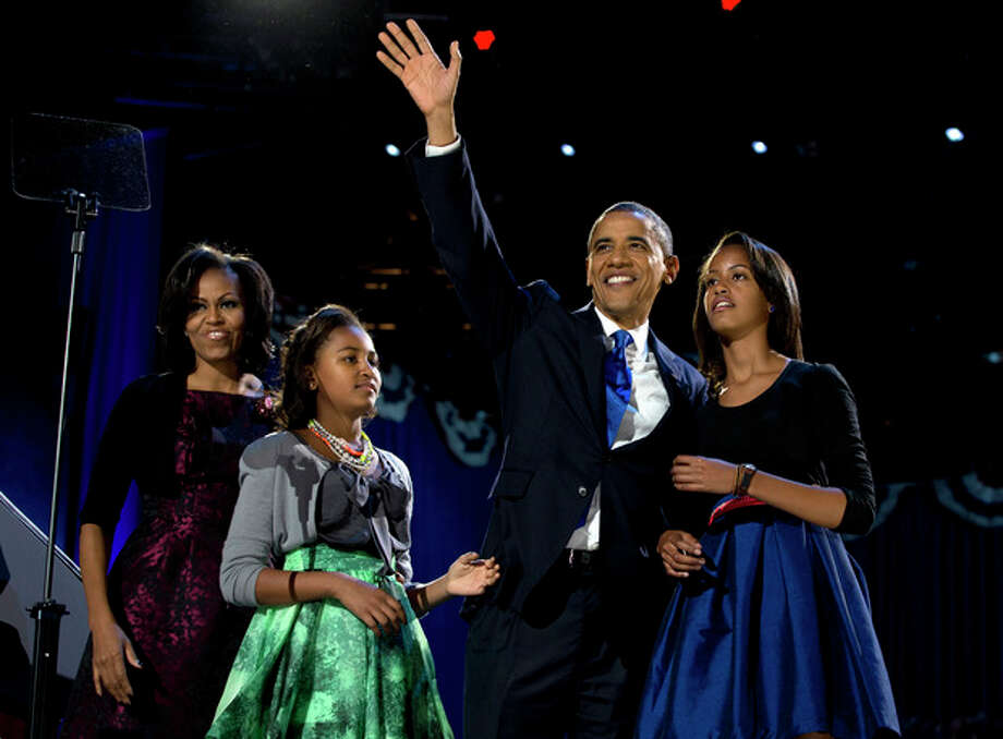 President Barack Obama waves as he walks on stage with first lady Michelle Obama and daughters Malia and Sasha at his election night party Wednesday, Nov. 7, 2012, in Chicago. Obama defeated Republican challenger former Massachusetts Gov. Mitt Romney. (AP Photo/Carolyn Kaster) / AP