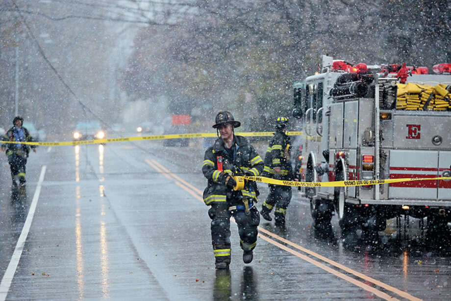 Norwalk firefighters respond to Strawberry Ave where downed wires closed the road Wednesday afternoon. Hour photo / Erik Trautmann / (C)2012, The Hour Newspapers, all rights reserved