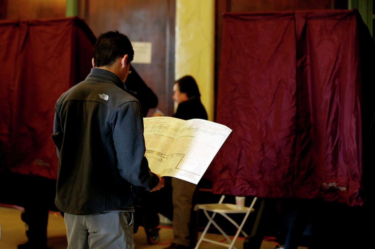 A person looks over a sample ballot while waiting to cast his vote on Election Day, Tuesday, Nov. 6, 2012, in Hoboken, N.J. (AP Photo/Julio Cortez)