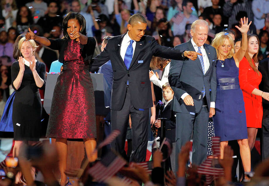 President Barack Obama , joined by his wife Michelle, Vice President Joe Biden and his spouse Jill acknowledge applause after Obama delivered his victory speech to supporters gathered in Chicago early Wednesday Nov. 7 2012. (AP Photo/Jerome Delay) / AP