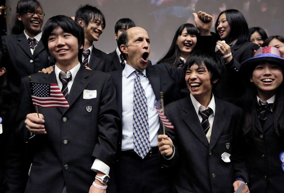 U.S. Ambassador to Japan John Roos, center, and Japanese high-school students celebrate reports that President Barack Obama won the presidential election at the U.S. Embassy in Tokyo Wednesday, Nov. 7, 2012. (AP Photo/Itsuo Inouye) / AP