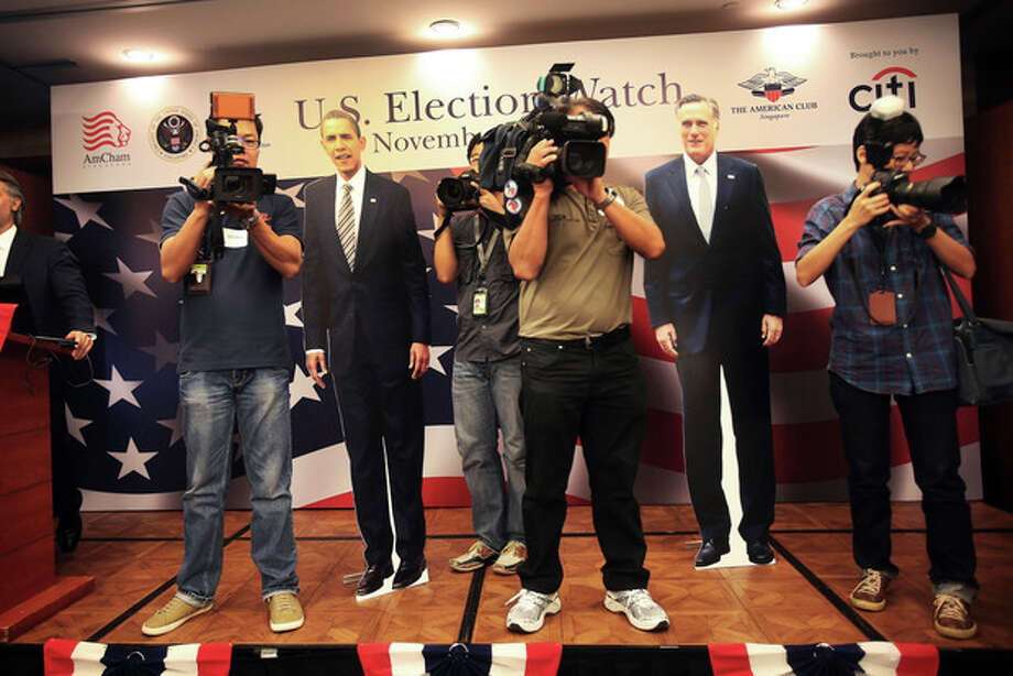 TV cameramen and photographers stand on stage with cutouts of U.S. Presidential candidates, Mitt Romney, right, and Barack Obama, as Americans and supporters gather at the American Club in Singapore to watch the live coverage of the election Wednesday, Nov. 7, 2012. (AP Photo/Wong Maye-E) / AP