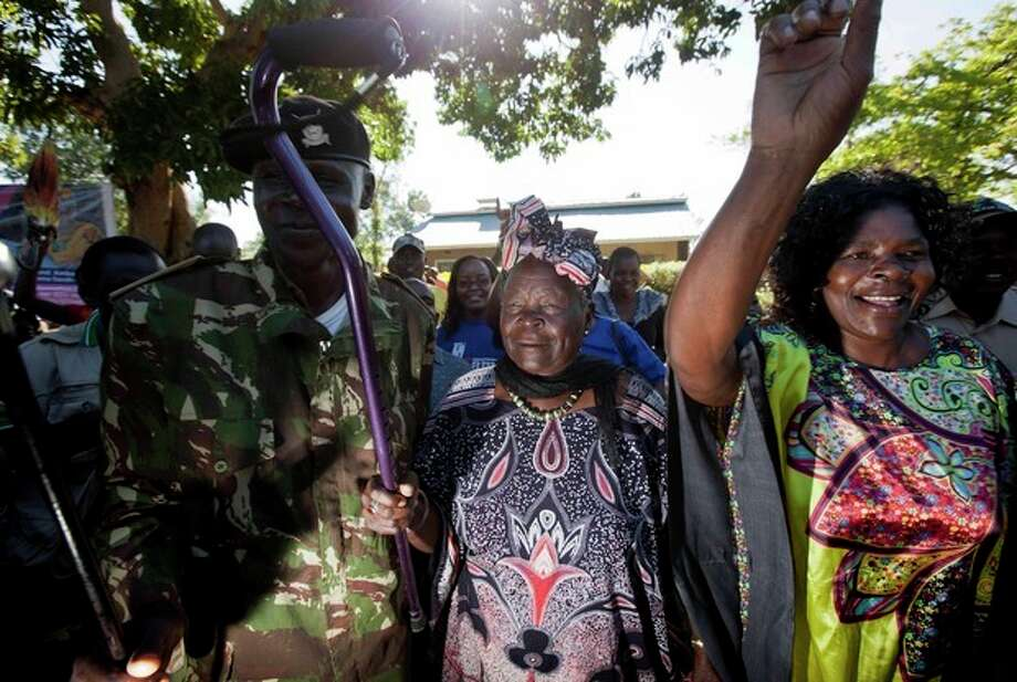 Sarah Obama, step-grandmother of President Barack Obama, waves her walking cane towards supporters in celebration before speaking to the media about her reaction to Obama's re-election in the U.S. presidential election in the garden of her house in the village of Kogelo, western Kenya, Wednesday, Nov. 7, 2012. (AP Photo/Ben Curtis) / AP