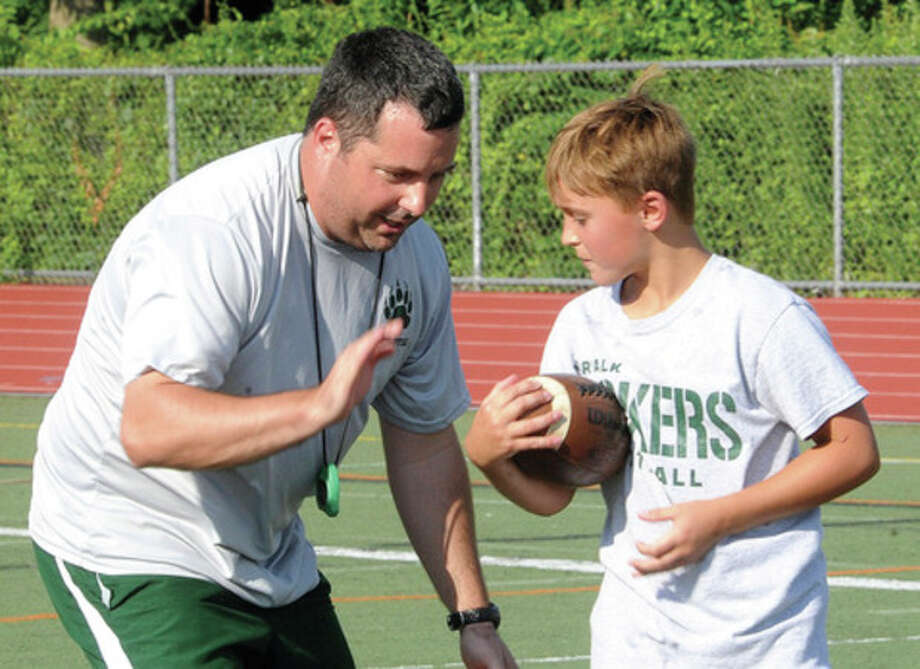 Hour photo/Matthew VinciNorwalk High football head coach Sean Ireland works with 11-year-old Patrick Coulter Monday at a youth football camp at Brien McMahon High School. In addition to helping out at the youth camp, Ireland -- like other area high schools coaches -- is busy laying the groundwork for this fall's scholastic campaign.