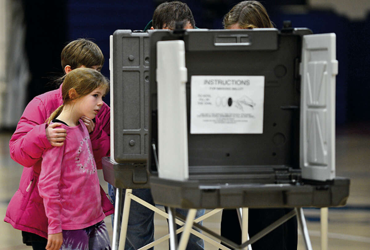 7 year old Wilton resident Charlotte Casiraghi and her family watches her father cast his ballot at Wilton High School Tuesday. Hour photo / Erik Trautmann