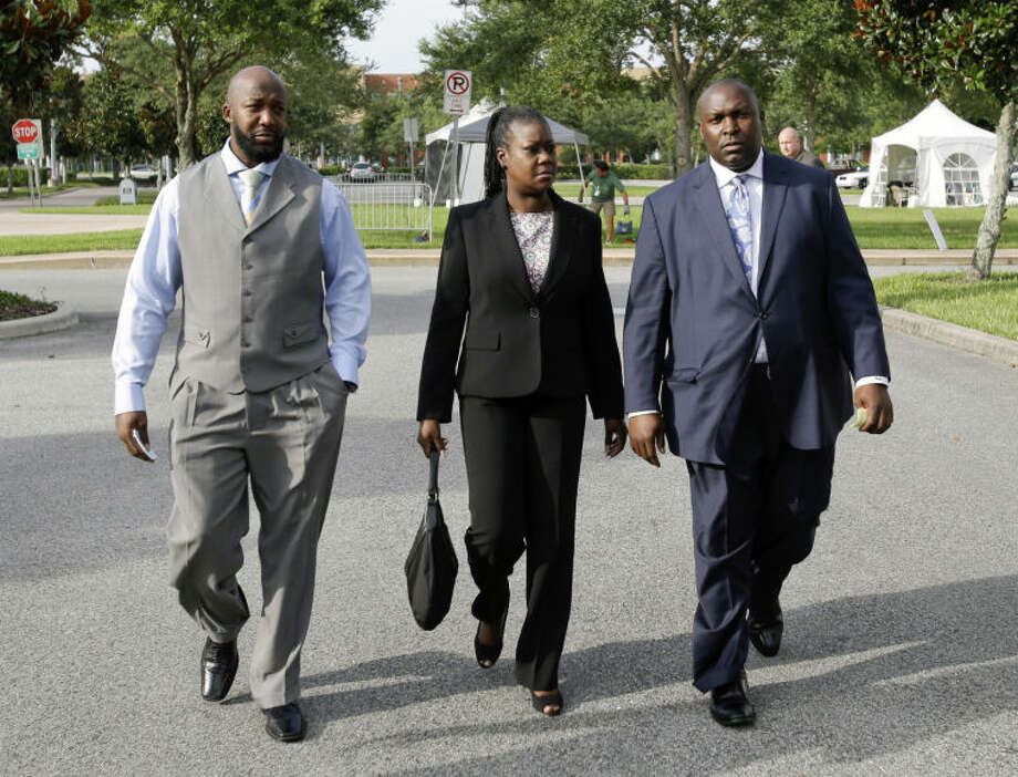 Tracy Martin, left, and Sybrina Fulton, center, parents of slain teen Trayvon Martin, leave the Seminole County Courthouse with their attorney Daryl Parks at the end of the day's proceedings in the trial of George Zimmerman, Thursday, June 27, 2013, in Sanford, Fla. Zimmerman has been charged with murder in the 2012 shooting death of Trayvon Martin. (AP Photo/John Raoux)