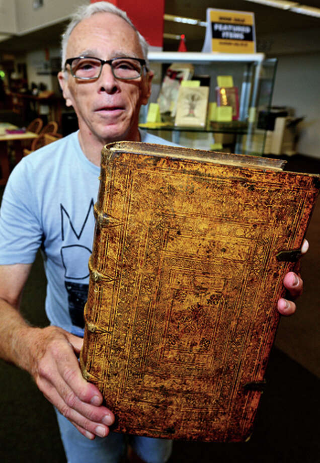 Volunteer and book sale organizer Dick Lowenstein holds a German Catholic Bible printed in 1610 that will be on sale at the Westport Public Library's 21st annual Summer Book Sale July 20-23. Hour photo / Erik Trautmann / (C)2013, The Hour Newspapers, all rights reserved