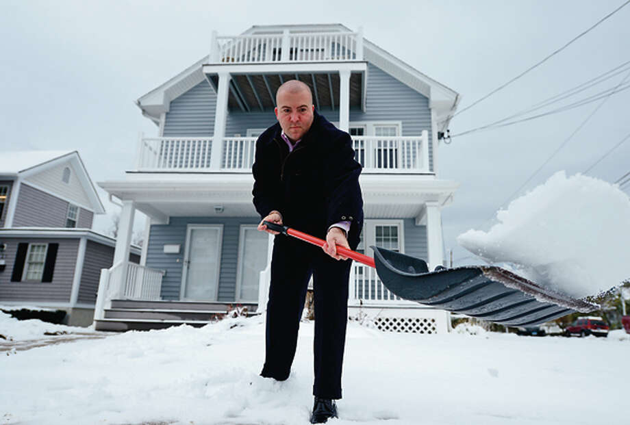 A week after a devastating hurricane Norwalk residents including Jason Intrieri clean up after a Nor' Easter left several inches of snow on the ground Thursday. Hour photo / Erik Trautmann / (C)2012, The Hour Newspapers, all rights reserved
