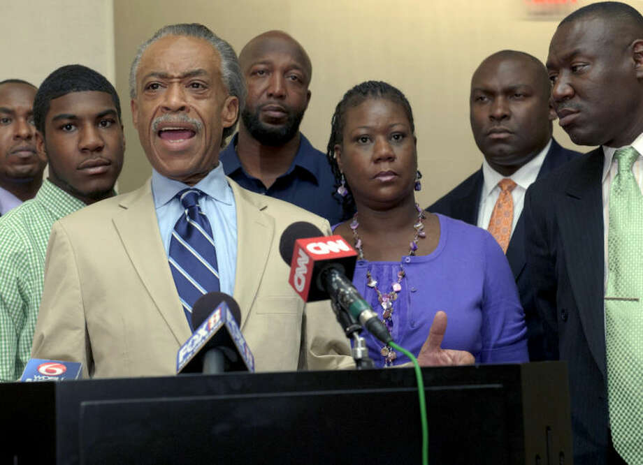 FILE- In this July 6, 2012 file photo, the Rev. Al Sharpton, left, speaks in front of Trayvon Martin's parents, father Tracy Martin, background center, and mother Sybrina Fulton, attorney Daryl D. Parks and attorney Benjamin L. Crump, attorneys for the family of Trayvon Martin, at the Hyatt Hotel in New Orleans. Fulton's other son Javaris Fulton is second from left. The jury in the trial of neighborhood watch volunteer George Zimmerman began deliberating his fate, Friday, July 12, 2013, on charges in the 2012 shooting death of unarmed teenager Trayvon Martin. (AP Photo/Matthew Hinton, File)