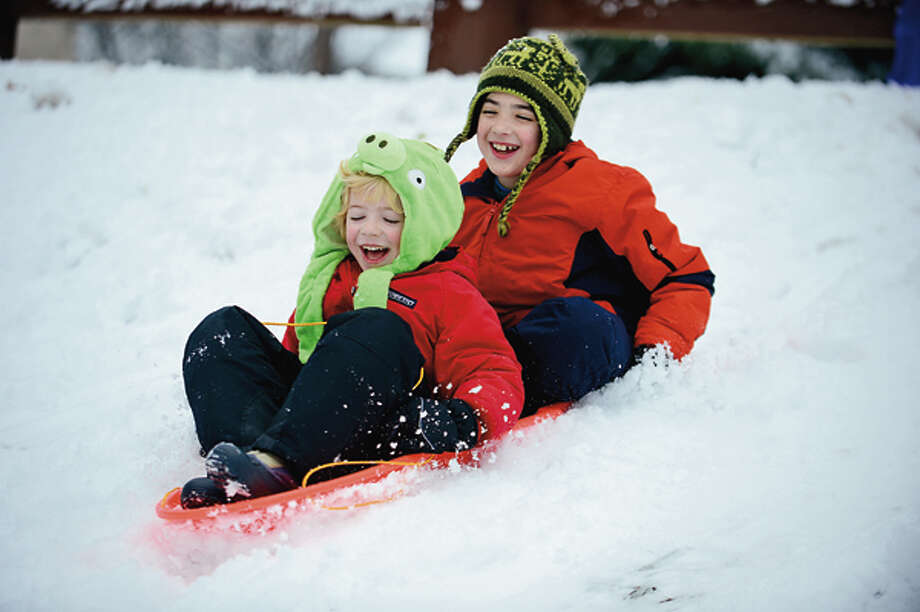 Brendan and Spencer Flahetty, 5 and 8, get some sledding in before school after a Nor' Easter left several inches of snow on the ground Thursday. Hour photo / Erik Trautmann / (C)2012, The Hour Newspapers, all rights reserved