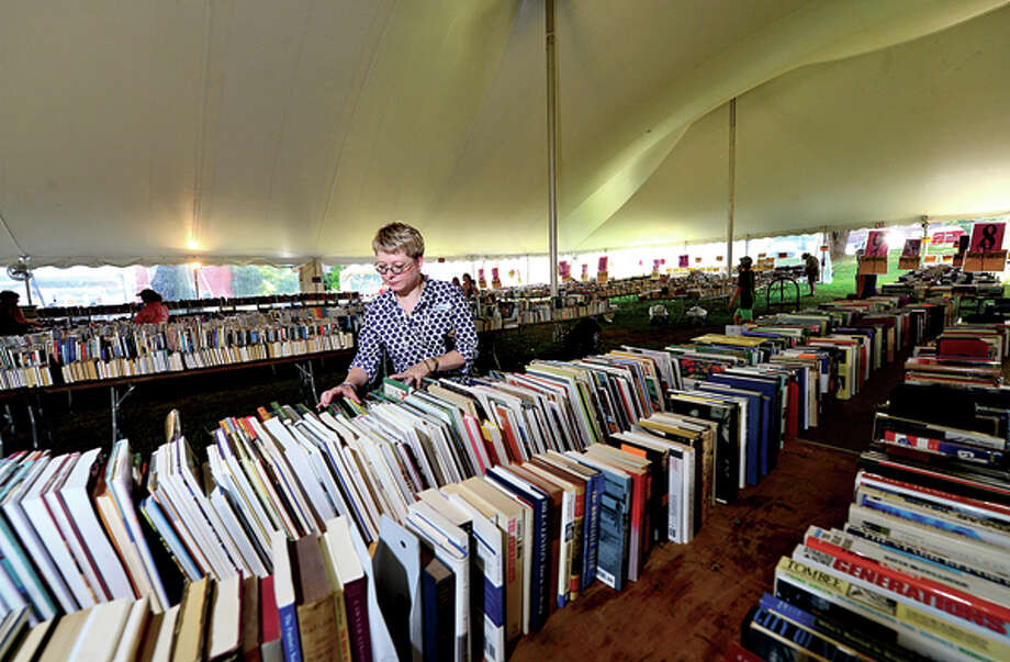Kelle Ruden, Community Relations Director for the Westport Public Library, sets up for their 21st annual Summer Book Sale July 20-23. Hour photo / Erik Trautmann / (C)2013, The Hour Newspapers, all rights reserved