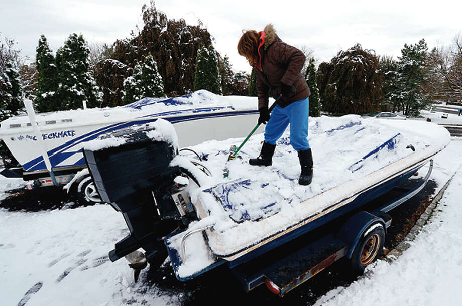 A week after a devastating hurricane Norwalk residents including Jane Randazzo clean up after a Nor' Easter left several inches of snow on the ground Thursday. Hour photo / Erik Trautmann / (C)2012, The Hour Newspapers, all rights reserved
