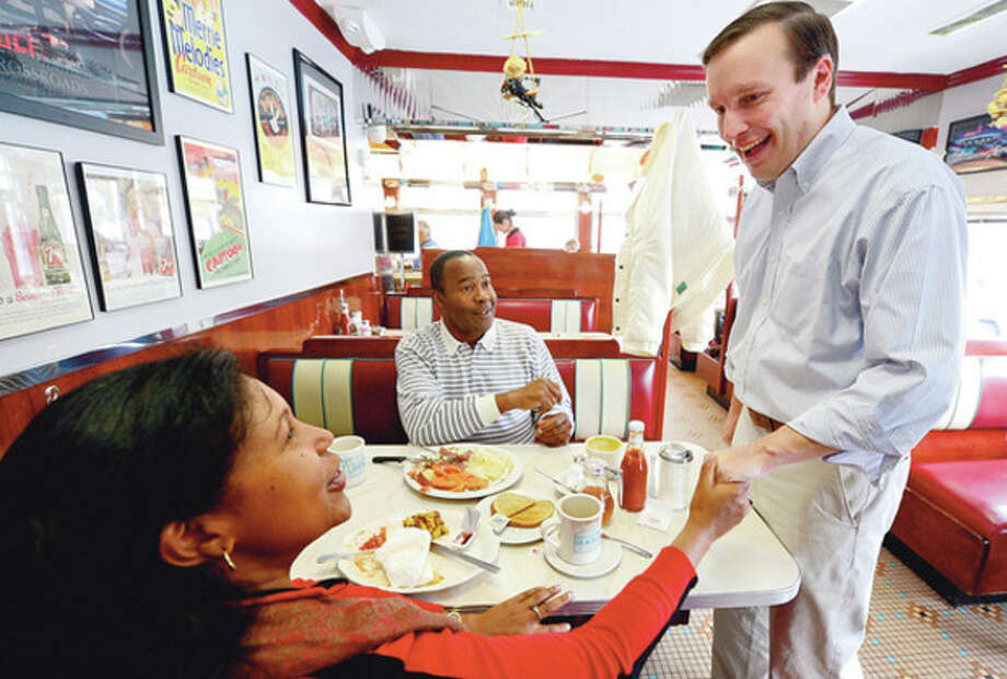 Norwalk resident Janet Evelyn and Stamford resident Tony Jay greet newly elected US Senator Chris Murphy at The Post RD Diner Thursday.Hour photo / Erik Trautmann / (C)2012, The Hour Newspapers, all rights reserved