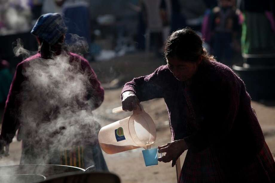A woman pours coffee during a funeral service for the Vasquez a family who was buried alive when their house collapsed during an earthquake in San Cristobal Cucho, Guatemala, Thursday, Nov. 8, 2012. The family died when a magnitude 7.4 earthquake struck on Wednesday, collapsing the home of the Vasquez and burying 10 of them, including a 4-year-old child, in the rubble. The powerful quake killed at least 52 people and left dozens more missing. Rescuers began employing heavy machinery early Thursday to search for more survivors. (AP Photo/Moises Castillo) / AP