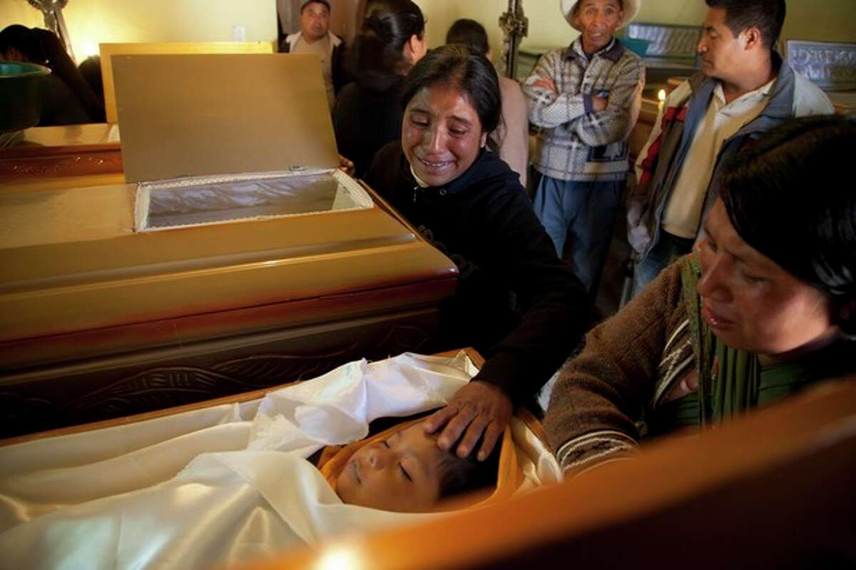 EDS NOTE GRAPHIC CONTENT - Nadalinis Juarez touches the forehead of her young nephew Dilbert Vazquez during a funeral service in San Cristobal Cucho, Guatemala, Thursday, Nov. 8, 2012. The 4-year-old died when a magnitude 7.4 earthquake struck on Wednesday, collapsing his home, burying him and 9 members of his family in the rubble. The powerful earthquake killed at least 48 people and left dozens more missing. Rescuers began employing heavy machinery early Thursday to search for more survivors. (AP Photo/Moises Castillo)