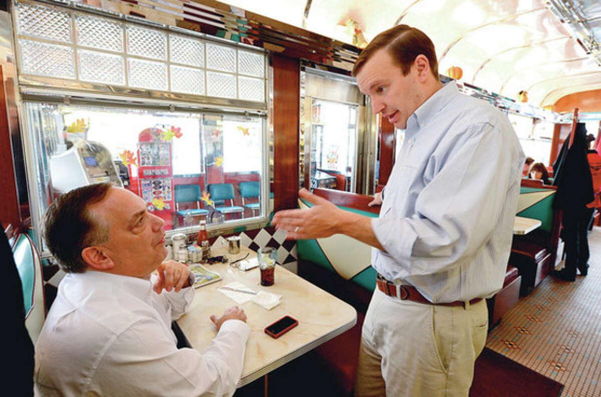 Hour photo / Erik Trautmann Stamford resident David Bauman greets newly elected Democratic U.S. Senator Chris Murphy at the Post Road Diner Thursday.