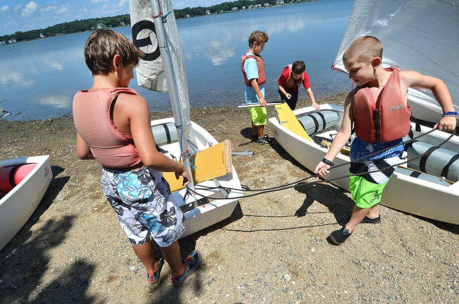 Brendan Sullivan and Zachary Tusa rig their sailboat at SoundWaters Opti Program summer camp sailing school.