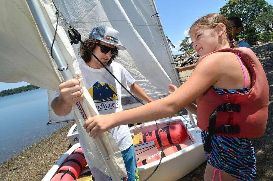 Lead Opti Instructor Joe Garan helps Hannah Becker with her sail during SoundWaters summer camp Opti Program sailing school.