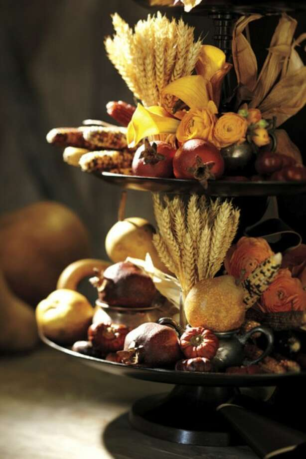 In this undated publicity photo provided by Pottery Barn, faux pomegranates available at Potterybarn.com add rich color to a cornucopia. They can be used year after year, and work in table displays well beyond Thanksgiving, into the winter holidays. (AP Photo/Pottery Barn)