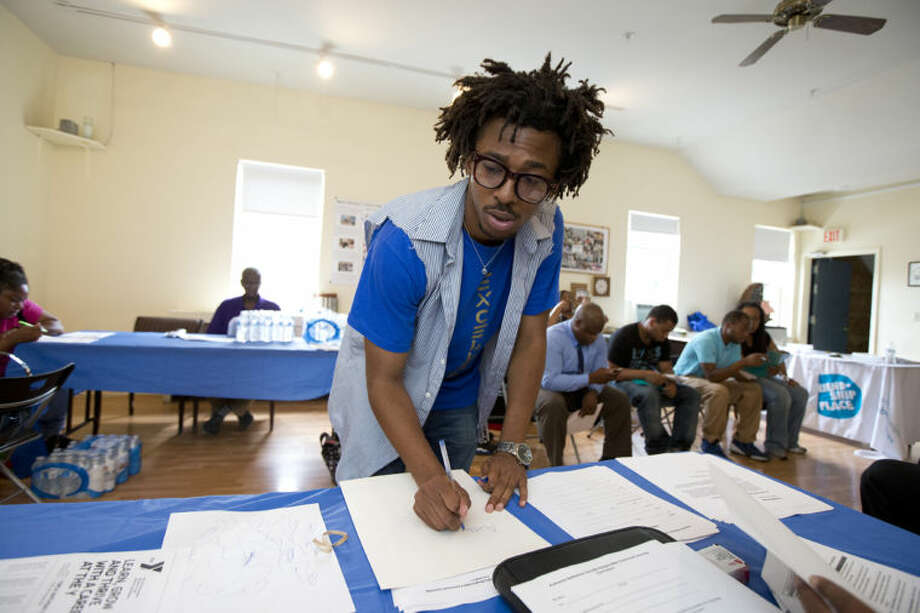 Americorps volunteer John Harris III, who is helping to coordinate a jobs fair program, fill up some documents for job seekers in Washington, Wednesday, July 31, 2013. AmericansÕ attitudes about their economic future are now sharply divided by race, with whites significantly less likely than blacks or Hispanics to think they can improve their own standard of living. Optimism among minorities now far outpaces that of whites, with the widest margin by race since at least 1987. The hopeful include John Harris III, 23, of Washington, a recent graduate of historically black Howard University who now works to reduce homelessness through the AmeriCorps program. (AP Photo/Manuel Balce Ceneta)