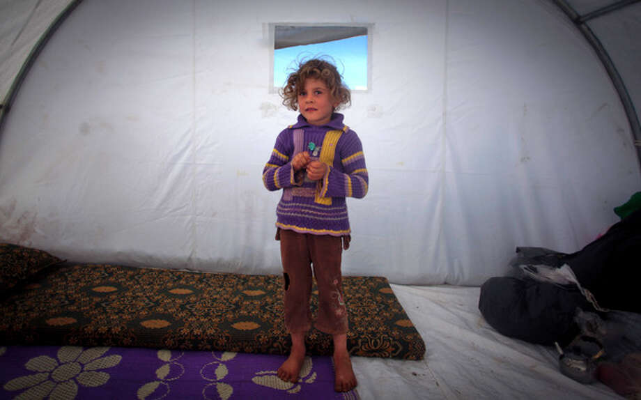 In this Wednesday, Nov. 7, 2012 photo, Shaymaa Al-Sadi, 6, who fled with her family from the violence in their village, poses for a photograph inside a tent at a displaced camp, in the Syrian village of Atmeh, near the Turkish border with Syria. Most of the displaced people in the tent camp rising near this village on the Syrian-Turkish border are children. All have fled the violence of Syria's civil war further south. Many have seen violence themselves, some have lost relatives, and most have trouble sleeping and panic when they hear loud noises or airplanes, their parents say. The Atmeh camp was born of necessity about three months ago, say the local rebels who run the place, distributing tents and food aid provided by a smattering of aid organizations.(AP Photo/ Khalil Hamra) / AP