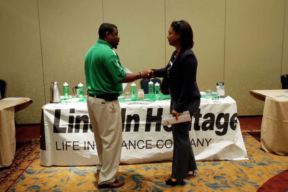 In this Monday, June 24, 2013, photo, job seeker Shawanda Strother, right, shakes hands with recruiter George McGlone III after a meeting at a career fair, in King of Prussia, Pa. The government reports on job openings and labor turnover for June on Tuesday, Aug. 6, 2013. (AP Photo/Matt Slocum) / AP