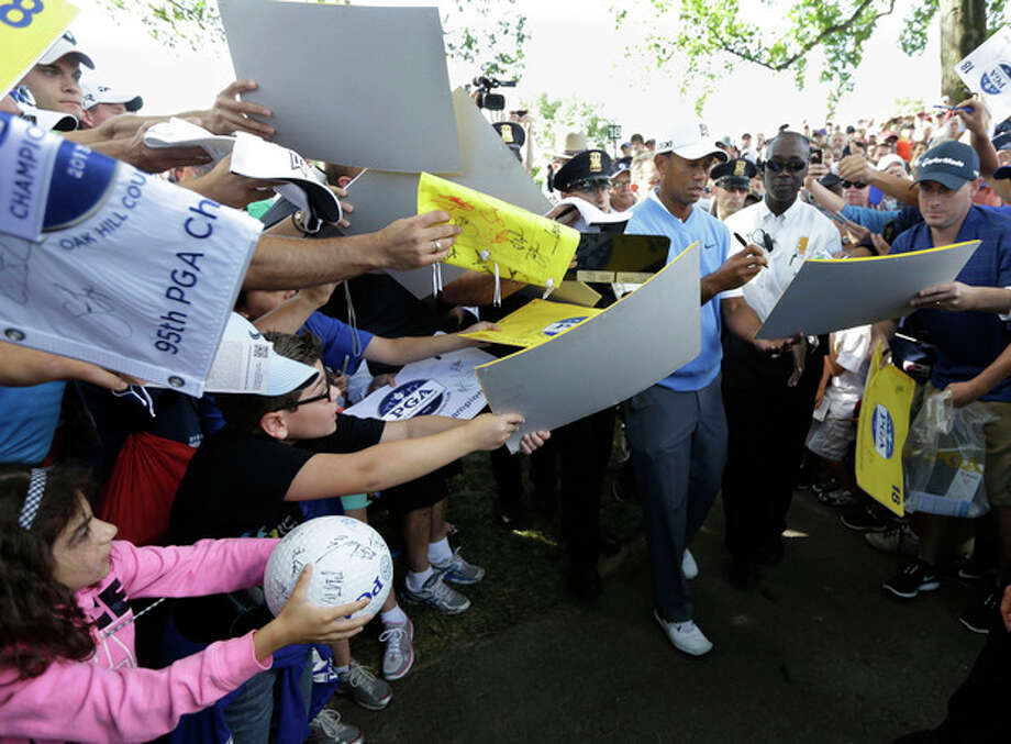 Tiger Woods signs autographs during a practice round for the PGA Championship golf tournament at Oak Hill Country Club, Tuesday, Aug. 6, 2013, in Pittsford, N.Y. (AP Photo/Charlie Neibergall) / AP