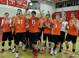 Ridgefield players celebrate following their 3-2 win over Darien in the Class L volleyball championship Thursday at Fairfield Warde High School.