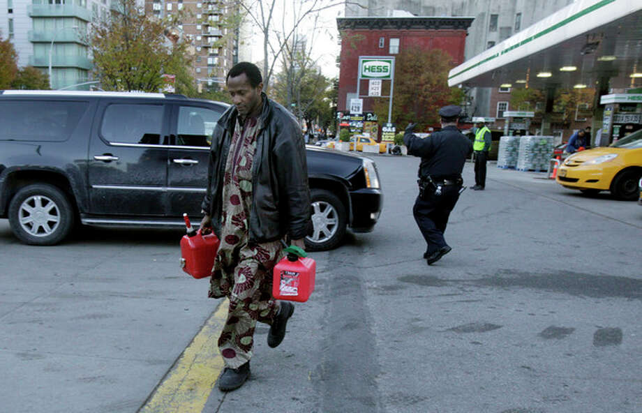 A man carries two filled gas cans at a gasoline station, in New York, Friday, Nov. 9, 2012. A new gasoline rationing plan that lets motorists fill up every other day went into effect in New York on Friday morning. Police were at gas stations to enforce the new system in New York City and on Long Island. (AP Photo/Richard Drew) / AP