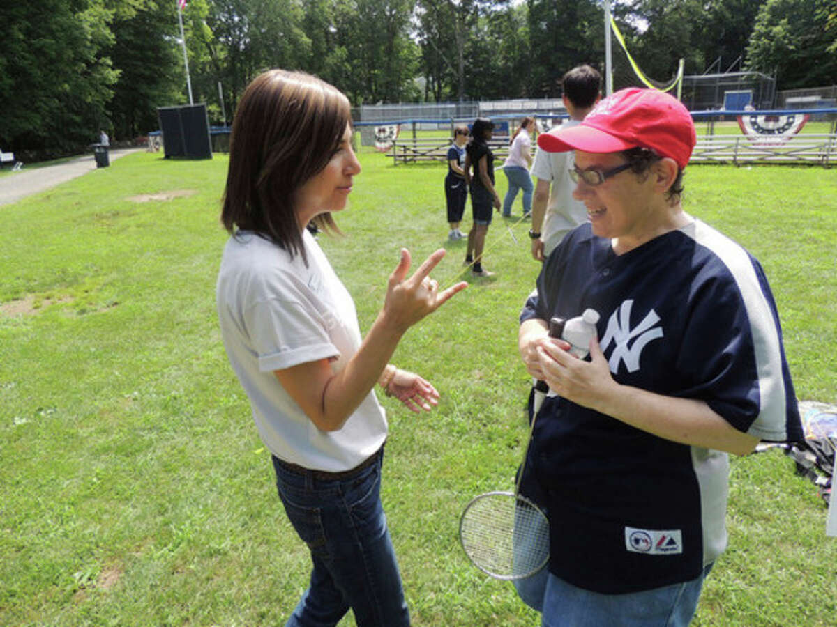 Contributed photo Tracey Rabb of STAR speaks sign language with GE volunteer Camila Londono.