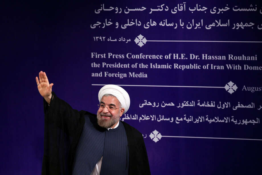 "Iran's new President Hasan Rouhani waves to reporters at the conclusion of his first press conference since taking office at the presidency compound in Tehran, Iran, Tuesday, Aug. 6, 2013. Rouhani says his country is ready for ""serious"" and swift talks with world powers over the nation's controversial nuclear program. (AP Photo/Ebrahim Noroozi) / AP"