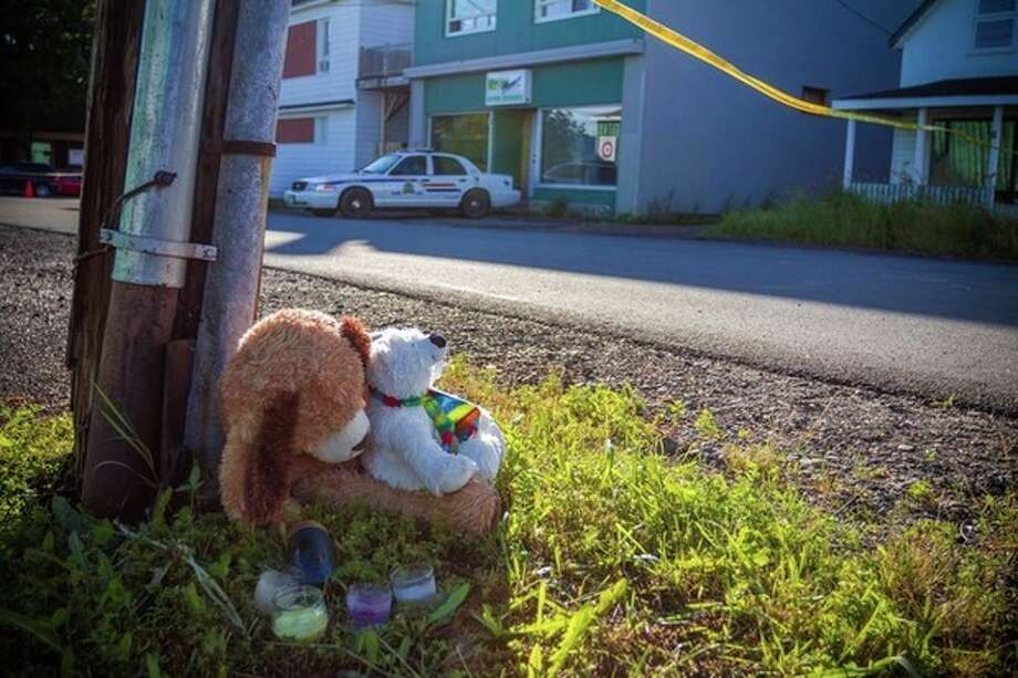 A memorial sits outside the Reptile Ocean exotic pet store in Campbellton, New Brunswick, Canada, on Tuesday, Aug. 6, 2013. Autopsies will be performed Tuesday on two young boys who were strangled in their sleep by a large African rock python that escaped from the pet store and slithered into the living room of an apartment upstairs from the pet store. (AP Photo/The Canadian Press, John LeBlanc) / The Canadian Press