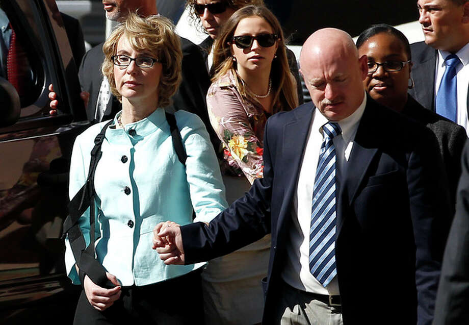 Former Democratic Rep. Gabrielle Giffords, left, and her husband Mark Kelly leave after the sentencing of Jared Loughner, in back of U.S. District Court Thursday, Nov. 8, 2012, in Tucson, Ariz. U.S. District Judge Larry Burns sentenced Jared Lee Loughner, 24, to life in prison, for the January 2011 attack that left six people dead and Giffords and others wounded. Loughner pleaded guilty to federal charges under an agreement that guarantees he will spend the rest of his life in prison without the possibility of parole. (AP Photo/Ross D. Franklin) / AP