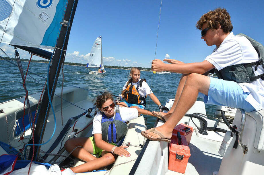 Hour Photo/Alex von Kleydorff . Sailing Coach Ber Evans goes over race 2 strategy with Skipper Claire Wagner and Crew Lindsay Walsh in the Norwalk Yacht Club entry during the Junior Sailing Associations Pixel Championship at Norwalk Yacht Club