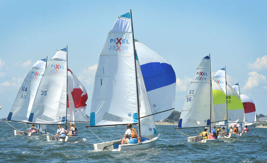 Hour Photo/Alex von Kleydorff. Pixel sailboats compete during the Junior Sailing Association's Pixel Championships at Norwalk Yacht Club, as the Norwalk Yacht Club entry looks for room with their spinnaker set