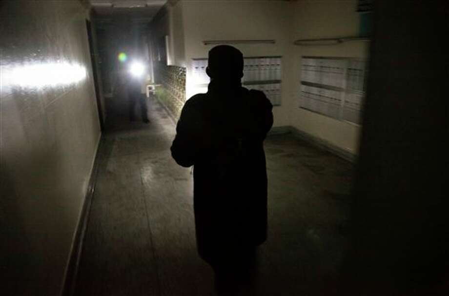 "Roxanne Boothe, right, use a flashlight as she walks a hallway at Sam Burt Houses, where she is president of the tenants association, checking residents on Saturday, Nov. 3, 2012 in Coney Island, N.Y. The complex, which has been without power since Monday, flooded during superstorm Sandy and a 90-year-old woman who had lived there for more than 40 years drowned on the first floor. ""We have no heat, no water, no electricity, it's dark in the whole building,"" said Boothe, frustrated that the Red Cross or FEMA assistance has not reached her neighborhood."" (AP Photo/Bebeto Matthews) / AP"