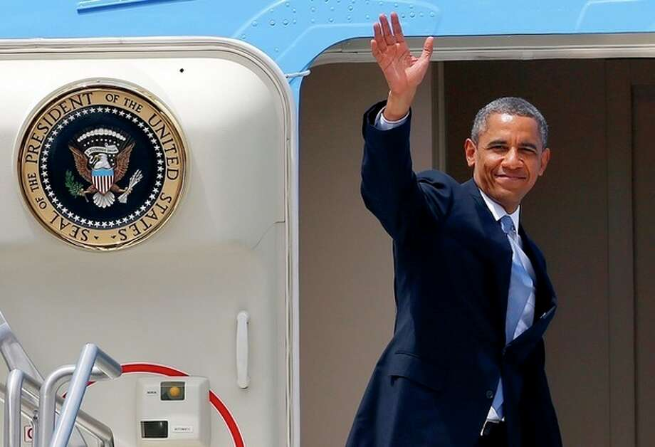 President Barack Obama waves from the steps of Air Force One as he prepares to depart Phoenix Sky Harbor International Airport after giving a speech on housing and the middle class on Tuesday, Aug. 6, 2013, in Phoenix. (AP Photo/Ross D. Franklin) / AP